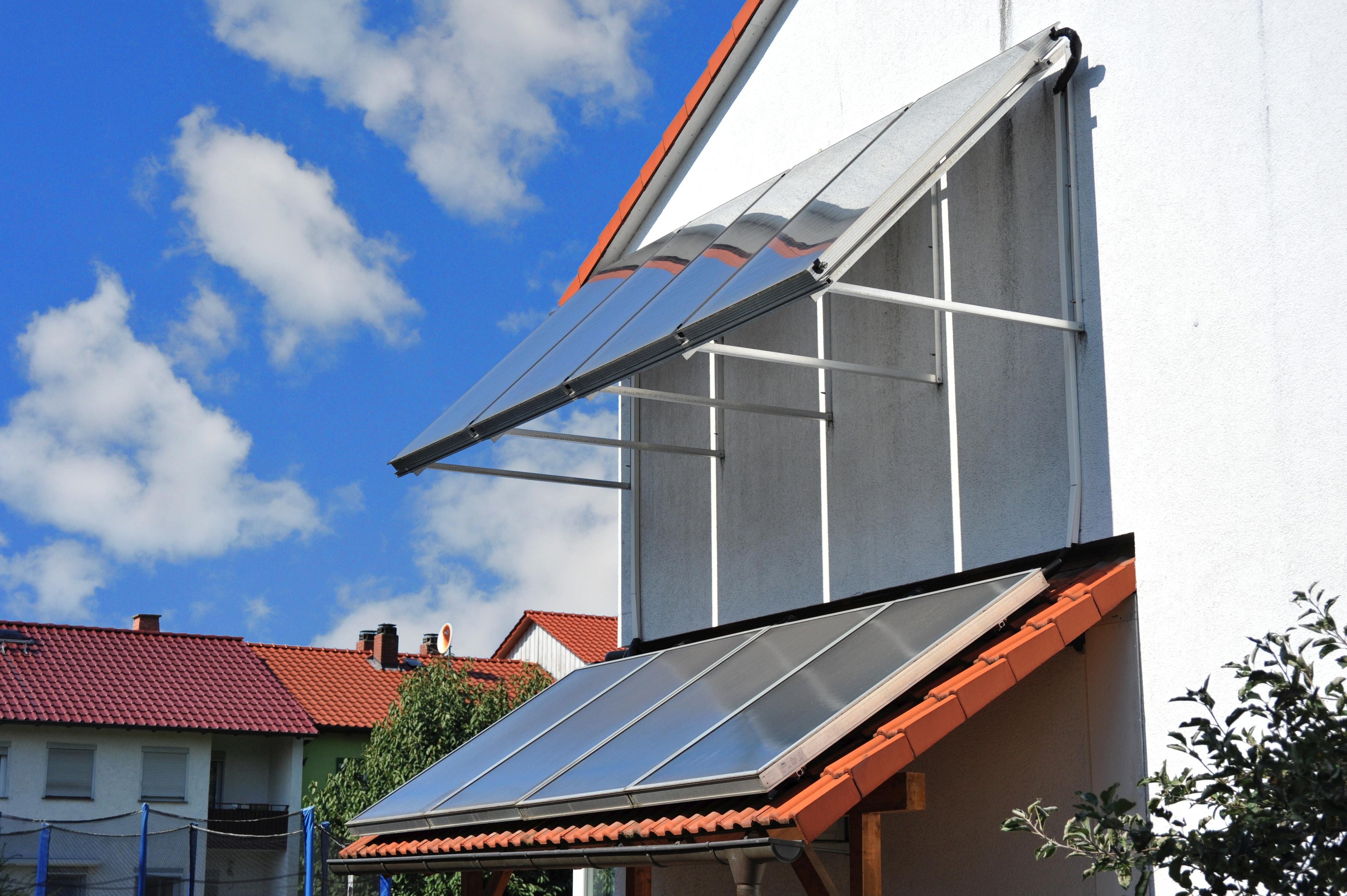 Sistema presurizado con colectores planos para agua caliente sanitaria y calefacción en un edificio multifamiliar en Alemania.