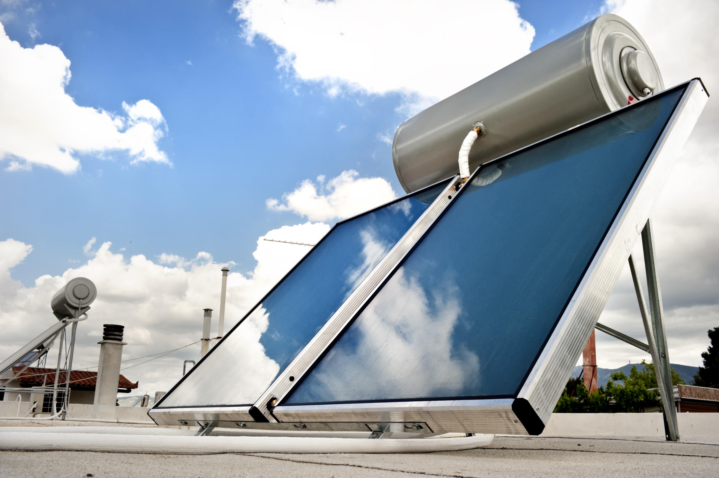 Sistema termosifónico con colectores solares planos para agua caliente sanitaria en un fraccionamiento residencial en Brasil.