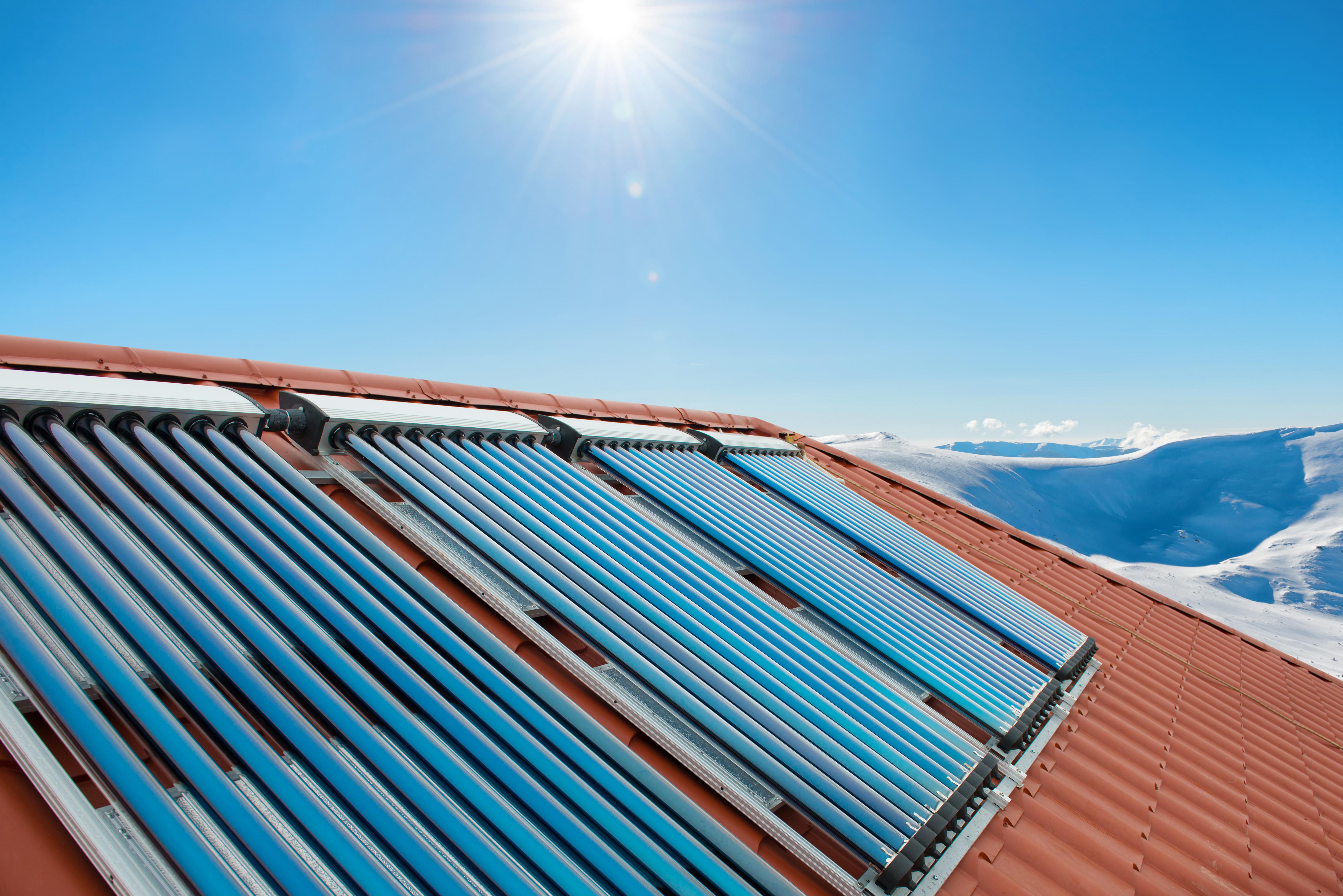 Sistema presurizado con colectores de tubos evacuados para calentamiento de agua sanitaria y calefacción en una cabaña en Suiza.